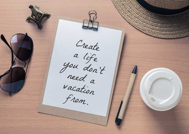 Afbeelding van papier met tekst 'create a life you don't need a vacation from'
